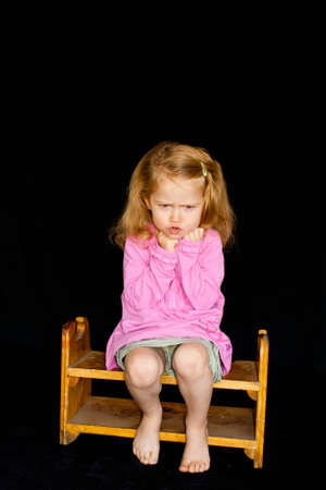 A cute girl pouting on a wooden stool. photo