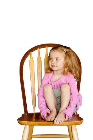 Een schattig meisje, zittend op een houten stoel met een witte achtergrond. Geïsoleerd