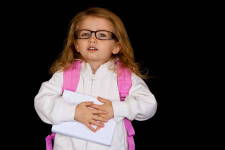 english girl: Girl with a backpack, glasses and a book.  The girl looks like she is going to learn.  The book is blank so the purchaser can put whatever title or description they want on it.