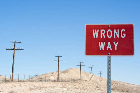 Wrong way sign with an old desert background photo