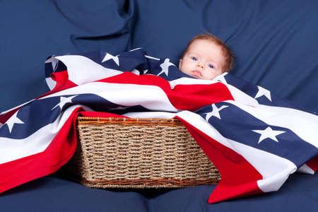Eine niedliche kleine Baby in einem Stroh Korb.  Das Baby ist mit das Flag-Muster als eine Decke und einen blauen Hintergrund hat. Standard-Bild - 8945929