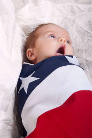 A cute baby wrapped up in a blanket with stars and stripes on it.  The baby is yawning.
