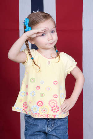 Cute girl saluting with a patriotic design in the background Standard-Bild