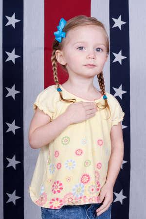 Adorable girl pledging alegiance in front of a patriotic design.