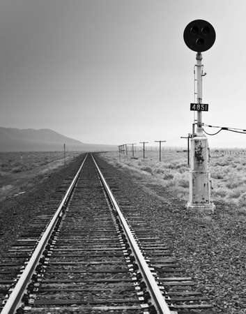 rule of thirds: A black and white photograph of an old fashioned railroad light and railroad.