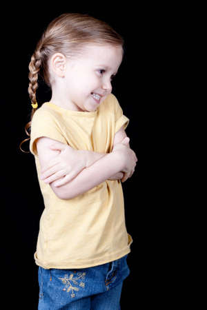 A girl with her arms crossed across her chest, she looks shy and aprehensive.
