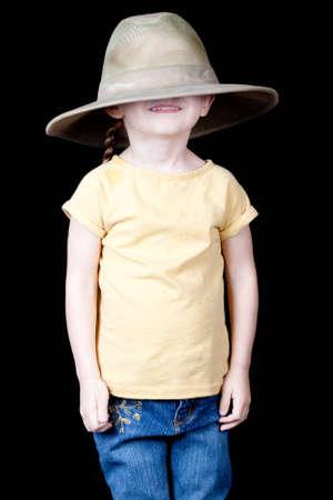 przewymiarowany: Cute Dziewczyna z zbyt duży kapelusz na głowę.  Jest on ściągnął nad jej oczu.