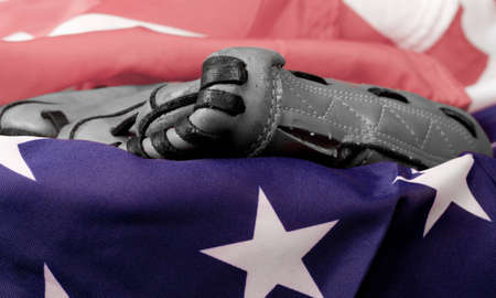 An old baseball glove in black and white and an American Flag. photo