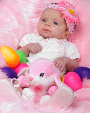 A cute infant girl on pink.  She has an easter bunny and a lot of easter eggs.
