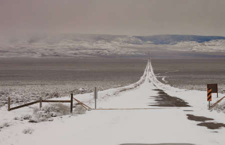 A landscape photograph of an icy snowy road.  The road leads through to the mountains.