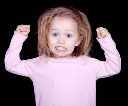 silliness: A kid throwing her fists up in anger.  She is acting out and misbehaving. Stock Photo