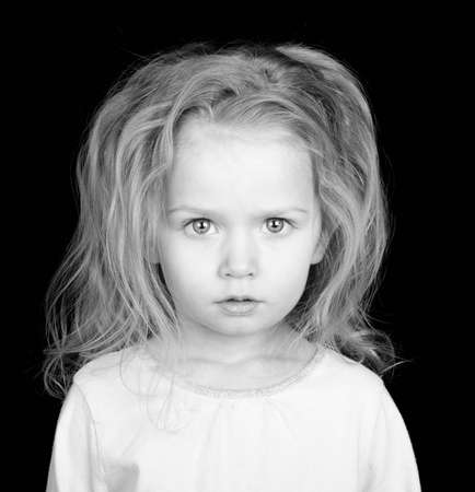 A poor missing child stares with her deep eyes at the viewer.  She is a starving child.