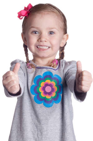 A cute young girl gives the viewer two thumbs up!  The thumbs are slightly out of focus which causes the viewers eye to be drawn to the excited look on the childs face. Stock Photo