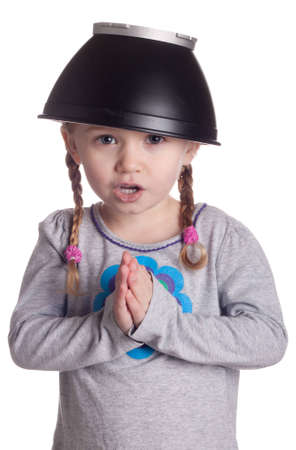 A young girl with a black metal style bowl hat on her head.  She is bowing before the viewer and pretending to be Chinese.