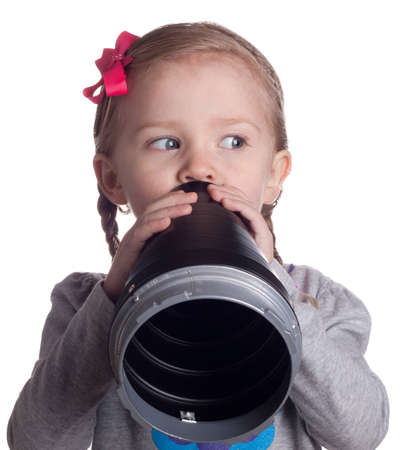 A very serious young child is talking secretly into her pretend microphone.  She is keeping an eye on someone so they do not see her. Imagens