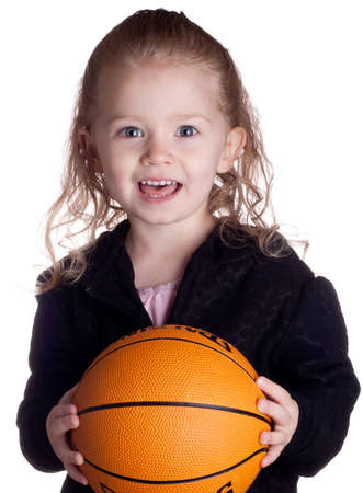 A cute girl is looking at the viewer asking if they want to play basketball.  She is very excited.