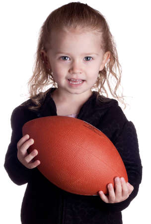 A child is holding a football asking the viewer if they would like to play too. Standard-Bild