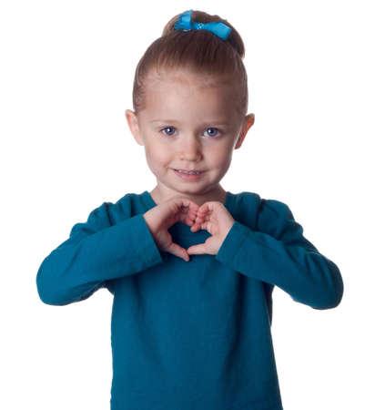 귀여운 어린 아이가 그녀의 손에 심장 모양을 형성합니다. 스톡 콘텐츠
