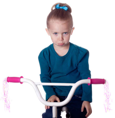 A girl is sad because she has to stop riding her bike. photo