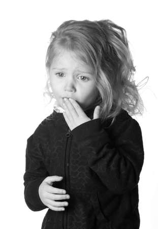 A black and white photograph of  a girl who could be expressing numerous emotions.