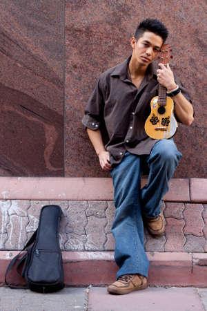 Una fotografia di un bel giovane con suo ukulele Archivio Fotografico - 9411684