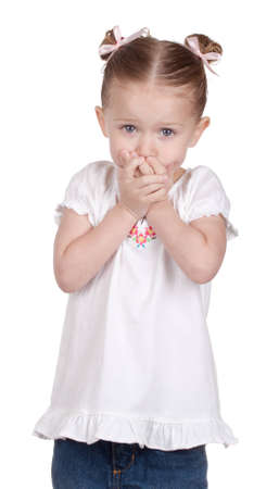 covering face: A girl is covering her mouth as if she is frightened.