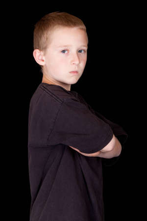 A photograph of a young boy with his arms crossed.