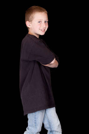 A boy is standing with his arms crossed and he is smiling. photo