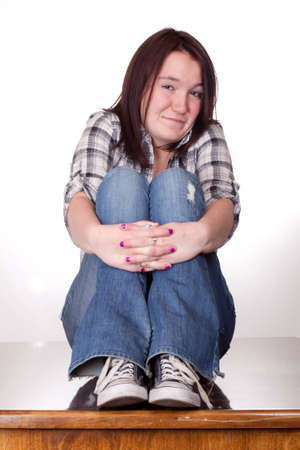 A photograph of a teenage girl with her legs up and hands folded with a smirk smile. Stock Photo - 9501505