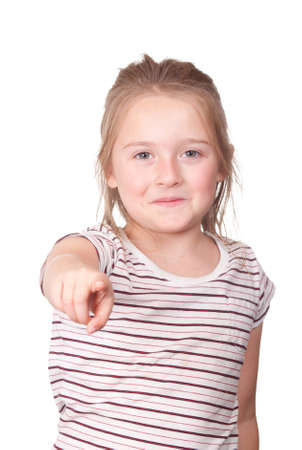 A photograph of a young girl pointing at something with a smirk on her face.