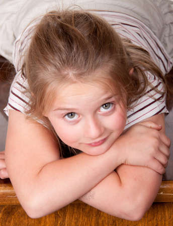A photograph of a young girl lying on a desk looking up at the world. photo