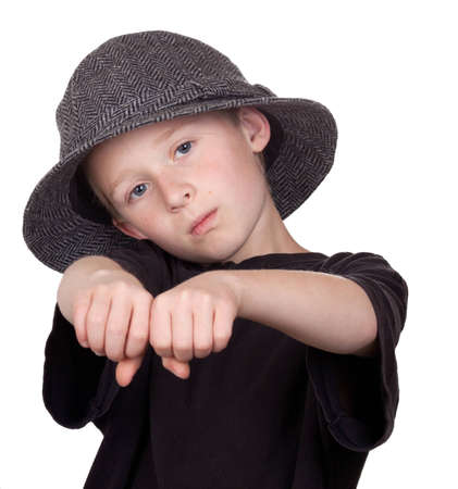 A photograph of a young boy with his knuckles showing while wearing his grey hat. photo