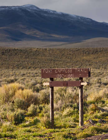 A beautiful photograph of a Pony Express Trail Sign with some nice snow capped mountains.