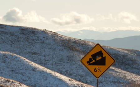 A six percent grade sign with some mountains in the background.