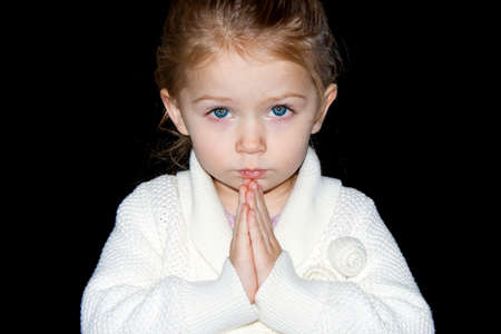 gods: A photograph of a young girl praying