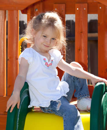 A photograph of an adorable child playing on some playground equipment. photo