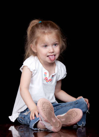A nice image of an adorable child sitting on some glossy wood with her tongue out.