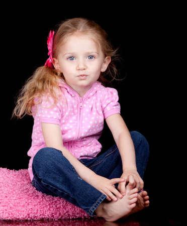 Ein Foto von einem hübschen Mädchen sitzt auf einem rosa Kissen. Standard-Bild - 9603098