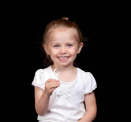 A very cute girl takes care of her teeth very well. Standard-Bild