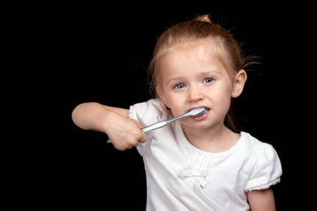 A very cute girl takes care of her teeth very well. Imagens