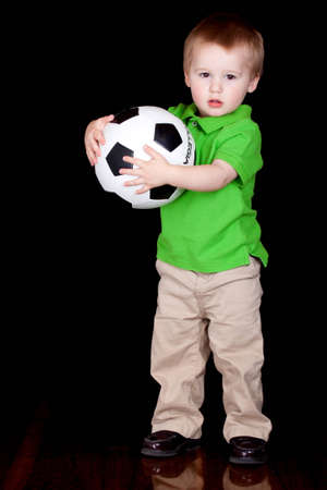 A cute child poses with his soccer ball.