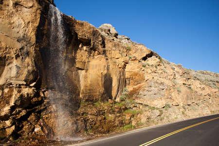 A nice image of a waterfall near a road. Standard-Bild