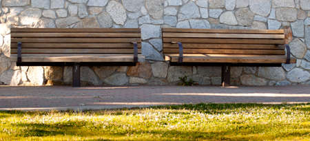 A great image of two empty benches.  The benches are wooden and they are in a nice park.