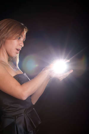 Image of a hispanic girl holding a mysterious ball of light. Standard-Bild