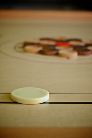 striker: Carrom striker with black and white coins Stock Photo