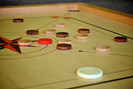 striker: Carrom game boards with black and white coins