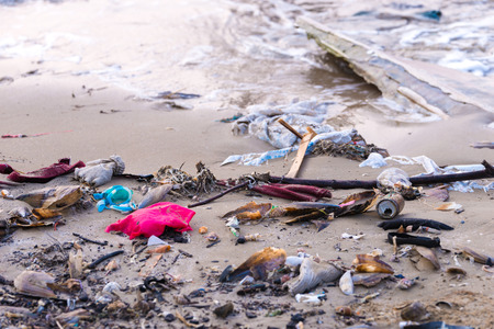 Beach pollution. Plastic bottles and other trash on sea beach Stock Photo