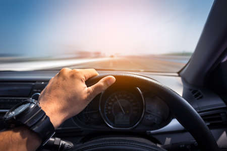 Man's hands of a driver on steering wheel of a minivan car on high way