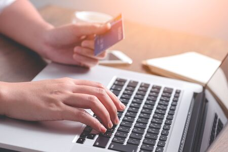 Close up hand holding credit card and using laptop. Online shopping Stock Photo
