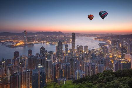 Hot balloon flying over Hong Kong city Stock Photo